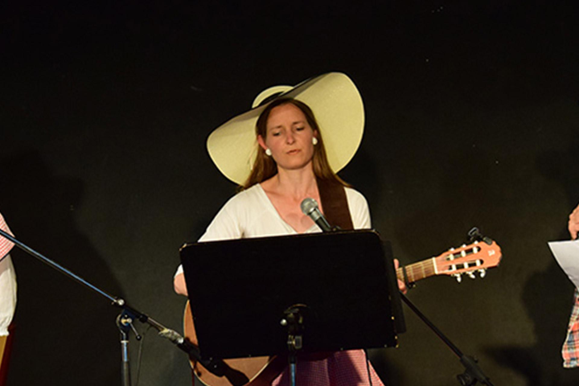 Abend der Poesie Montessori Schule Peißenberg: Eine Schülerin spielt Gitarre und singt.